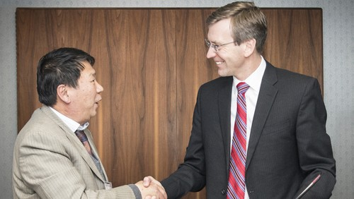 Left to right: Zhang Tao, Secretary of CPC Committee and President of Yunnan Tin Company, and Ross Berntson, Indium Corporation Executive Vice President, shake hands after signing an agreement to form a strategic technology and materials partnership between the two companies.